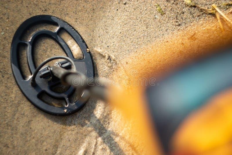 Μέρος του ανιχνευτή μετάλλων στο πρώτο πλάνο θόλωσε και της συσκευής σπειρών στην άμμο, αναζήτηση μετάλλων το καλοκαίρι στοκ εικόνα με δικαίωμα ελεύθερης χρήσης