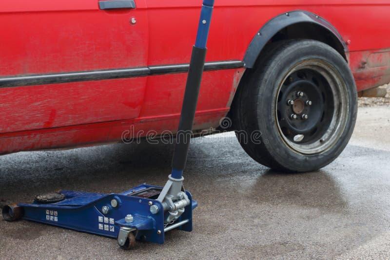 Μέρος του αυτοκινήτου και του εργαλείου για την επισκευή αυτοκινήτων - ισοπεδώνοντας γρύλος στοκ εικόνες