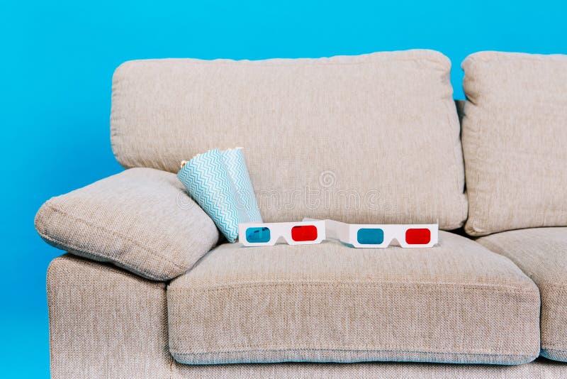 Μέρος του γκρίζου καναπέ με τα τρισδιάστατα γυαλιά και popcorn στο μπλε υπόβαθρο Απολαμβάνοντας τον κινηματογράφο στο σπίτι, να π στοκ φωτογραφία