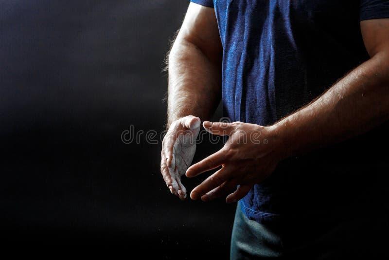 Μέρος του κορμού του ανθρώπου, φορέστε μαύρο μπλουζάκι με τα χέρια καλυμμένα με σκόνη ταλκ στοκ φωτογραφία