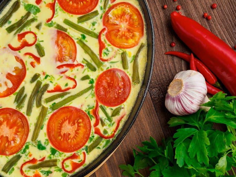Μέρος του τηγανιού χυτοσιδήρου με τα ανακατωμένα αυγά, ντομάτες και othe στοκ εικόνες