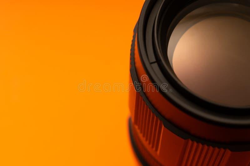 Μέρος του φακού φωτογραφιών στο πορτοκαλί υπόβαθρο στοκ εικόνες