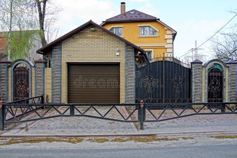 Μέρος του φράκτη με μια πύλη σιδήρου και ένα γκρίζο γκαράζ κοντά στο δρόμο στην οδό στοκ φωτογραφίες