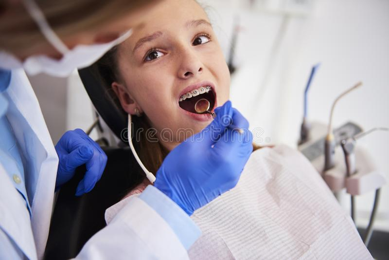 Μέρος του orthodontist που εξετάζει τα δόντια του παιδιού στο γραφείο του οδοντιάτρου στοκ εικόνα