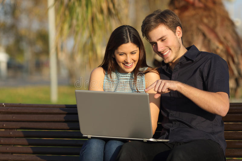 Μέσα προσοχής ζεύγους σε μια συνεδρίαση lap-top σε έναν πάγκο στοκ εικόνες με δικαίωμα ελεύθερης χρήσης