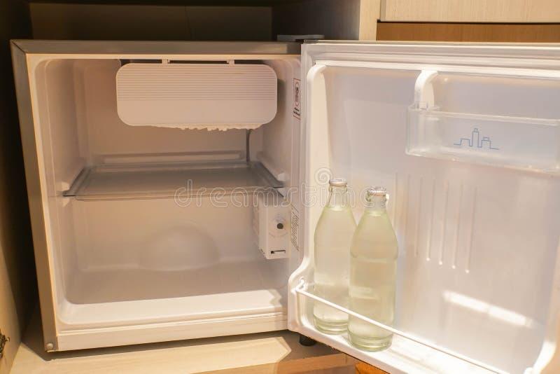 Μέσα στο μίνι ψυγείο στην κρεβατοκάμαρα ξενοδοχείων με το μπουκάλι νερό στοκ εικόνες με δικαίωμα ελεύθερης χρήσης
