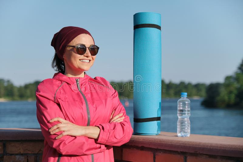 Μέσης ηλικίας βέβαια αθλήτρια με το χαλί γιόγκας και μπουκάλι νερό με τα διασχισμένα διπλωμένα όπλα στοκ φωτογραφία με δικαίωμα ελεύθερης χρήσης
