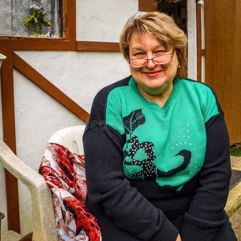 Μέσης ηλικίας γυναίκα με τα γυαλιά που στηρίζονται στο πάρκο στοκ φωτογραφία