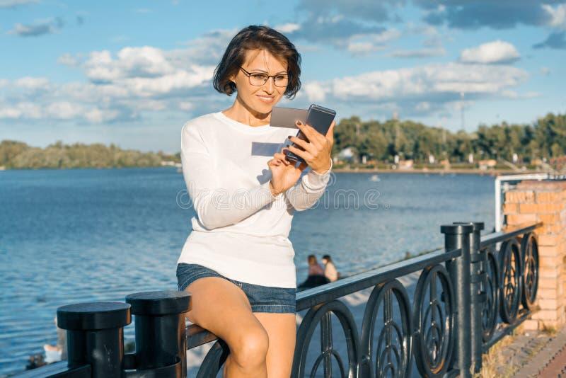 Μέσης ηλικίας γυναίκα με το κινητές τηλέφωνο και τη επαγγελματική κάρτα Θηλυκό smartphone χρήσεων που εξετάζει την κάρτα στοκ φωτογραφίες