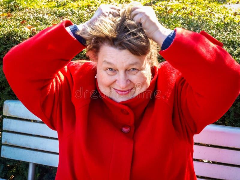 Μέσης ηλικίας γυναίκα σε ένα κόκκινο παλτό που στηρίζεται στο πάρκο στοκ εικόνες με δικαίωμα ελεύθερης χρήσης
