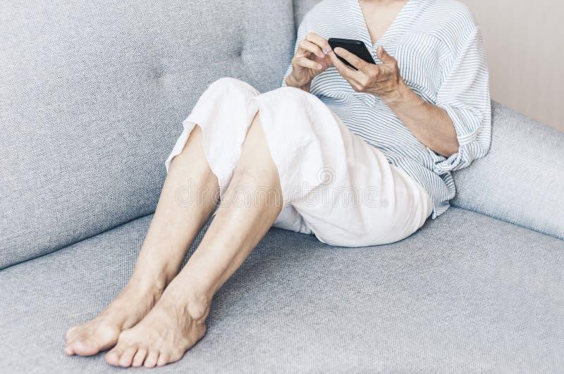 Μέσης ηλικίας γυναίκα στο γκρίζο smartphone χρήσης καναπέδων στοκ φωτογραφία