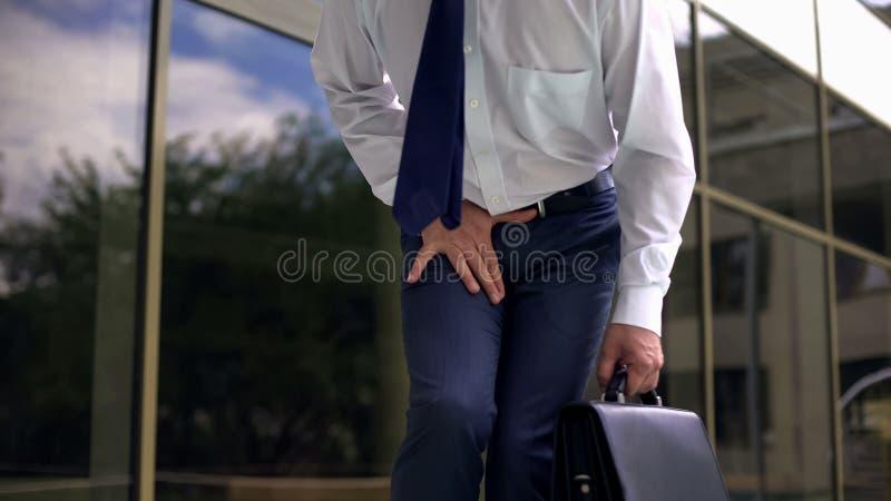 Μέσης ηλικίας διευθυντής που αισθάνεται τον ισχυρό πόνο, prostatitis, ανδρική γεννητική ασθένεια στοκ φωτογραφία