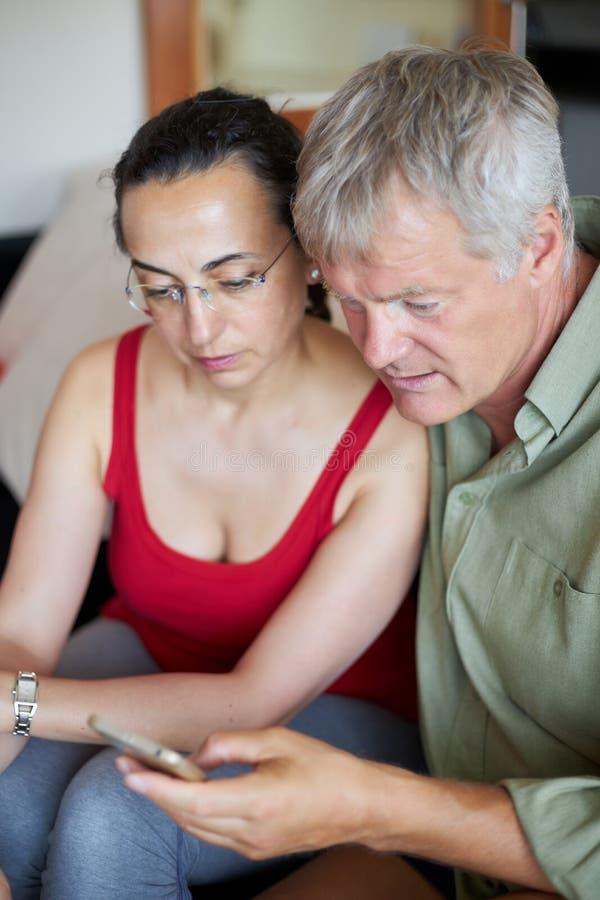 Μέσης ηλικίας ζεύγος που φαίνεται ένα κινητό τηλέφωνο στοκ φωτογραφία με δικαίωμα ελεύθερης χρήσης
