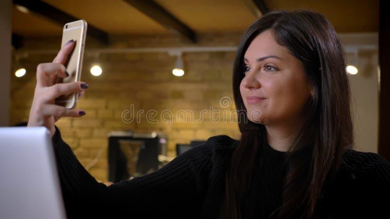 Μέσης ηλικίας υπέρβαρη γυναίκα μπροστά από το lap-top που κάνει τις selfie-φωτογραφίες που χρησιμοποιούν πρόθυμα το smartphone στ στοκ φωτογραφία