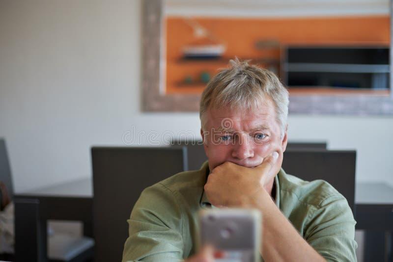 Μέσης ηλικίας όμορφο άτομο στο σπίτι με το έξυπνο τηλέφωνο κινητό στοκ φωτογραφίες