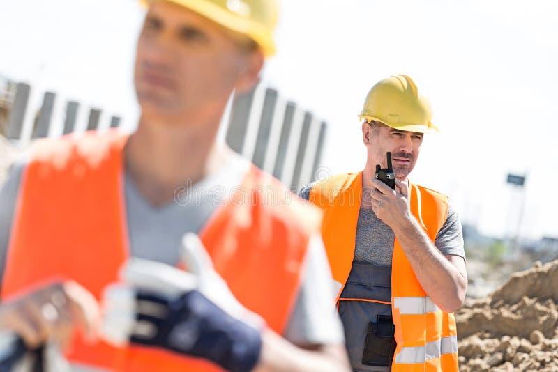Μέσης ηλικίας άνδρας εργαζόμενος που χρησιμοποιεί walkie-talkie με το συνάδελφο στο πρώτο πλάνο στο εργοτάξιο οικοδομής στοκ εικόνα