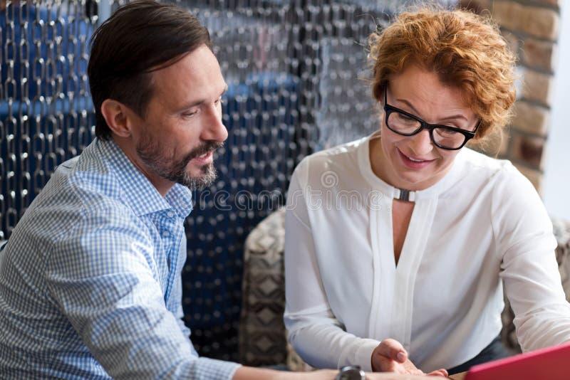 Μέσης ηλικίας άνδρας και γυναίκα που συζητούν τις πληροφορίες από το lap-top στοκ φωτογραφίες με δικαίωμα ελεύθερης χρήσης