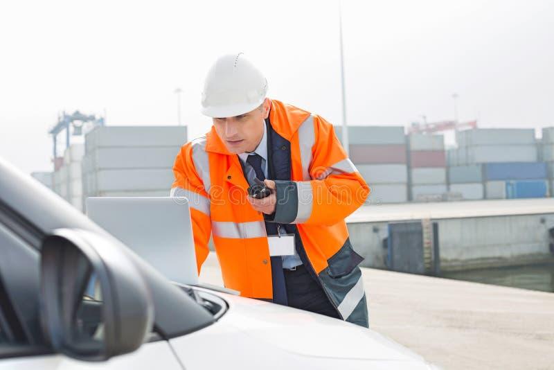 Μέσης ηλικίας άτομο που μιλά walkie-talkie χρησιμοποιώντας το lap-top στη ναυτιλία του ναυπηγείου στοκ φωτογραφία