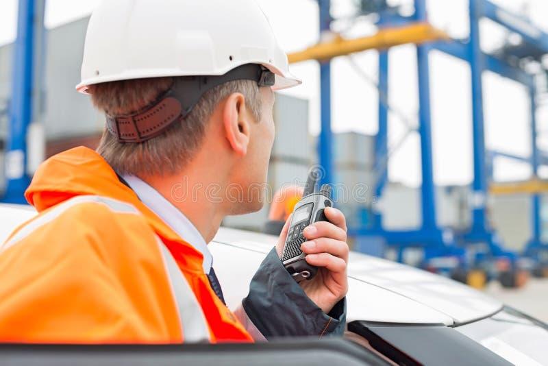 Μέσης ηλικίας άτομο που χρησιμοποιεί walkie-talkie στεμένος εκτός από το αυτοκίνητο στη ναυτιλία του ναυπηγείου στοκ φωτογραφία με δικαίωμα ελεύθερης χρήσης