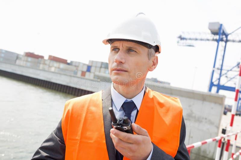 Μέσης ηλικίας άτομο που χρησιμοποιεί walkie-talkie στη ναυτιλία του ναυπηγείου στοκ φωτογραφία με δικαίωμα ελεύθερης χρήσης