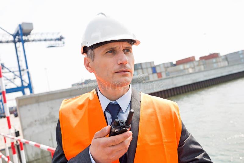 Μέσης ηλικίας άτομο που χρησιμοποιεί walkie-talkie στη ναυτιλία του ναυπηγείου στοκ εικόνες