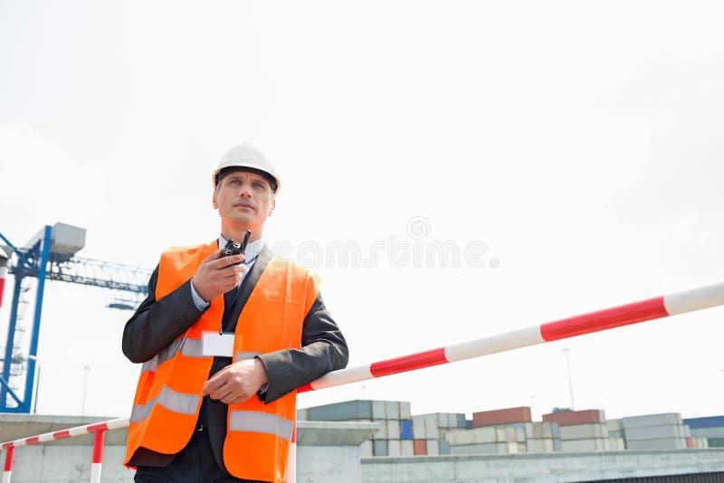 Μέσης ηλικίας άτομο που χρησιμοποιεί walkie-talkie στη ναυτιλία του ναυπηγείου στοκ εικόνα με δικαίωμα ελεύθερης χρήσης