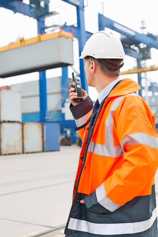 Μέσης ηλικίας άτομο που χρησιμοποιεί walkie-talkie στη ναυτιλία του ναυπηγείου στοκ φωτογραφίες με δικαίωμα ελεύθερης χρήσης