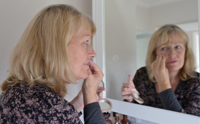 Μέσης ηλικίας γυναίκα που εφαρμόζει τη σκόνη προσώπου στοκ εικόνες