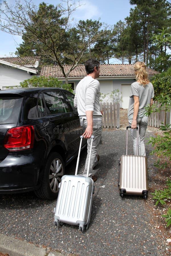 Μέσης ηλικίας ζεύγος που προέρχεται κατ' οίκον από τις διακοπές στοκ εικόνες