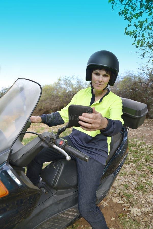 Μέσης ηλικίας καθρέφτης ρύθμισης γυναικών στη μοτοσικλέτα στοκ φωτογραφία με δικαίωμα ελεύθερης χρήσης