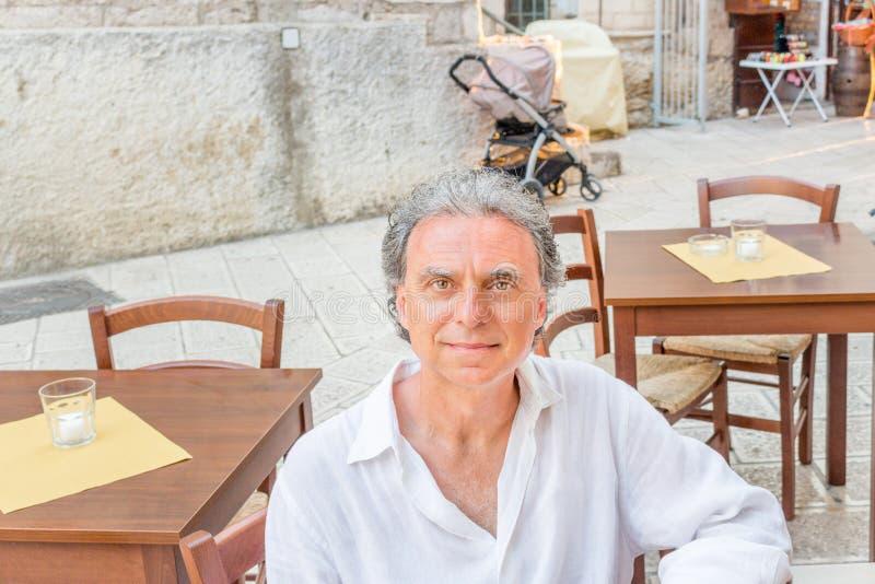 Μέσης ηλικίας συνεδρίαση ατόμων στο εστιατόριο στοκ φωτογραφίες