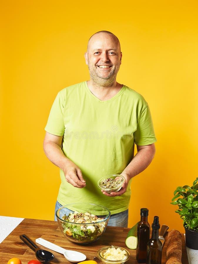 Μέσης ηλικίας φρέσκια σαλάτα μαγείρων ατόμων στοκ εικόνα