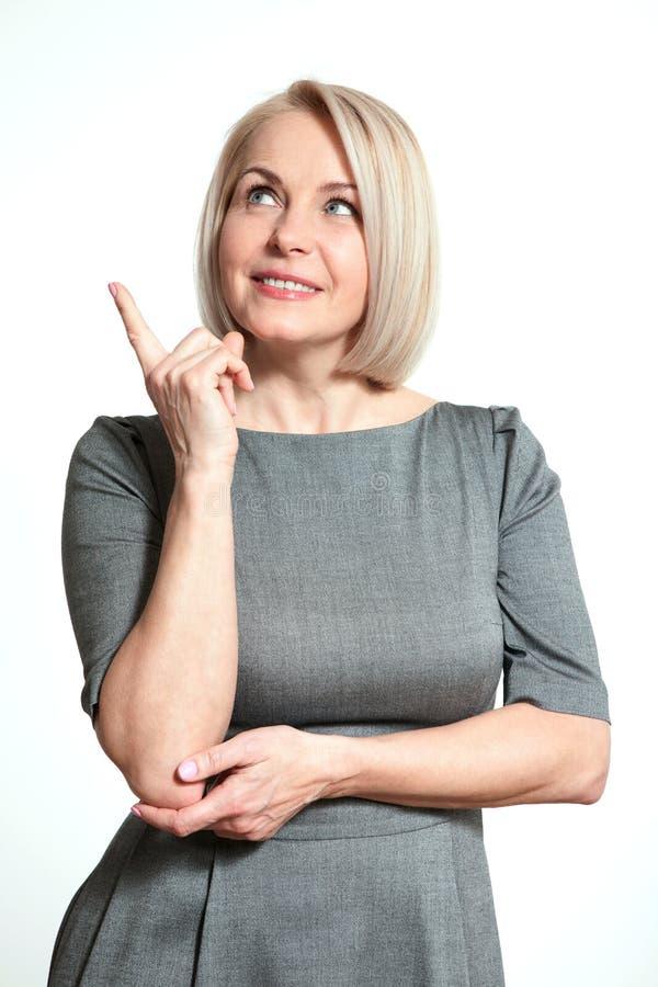 Μέσης ηλικίας όμορφη γυναίκα που φαίνεται επάνω σκεπτόμενη και ονειρεμένος που απομονώνεται στο άσπρο υπόβαθρο στοκ εικόνες με δικαίωμα ελεύθερης χρήσης