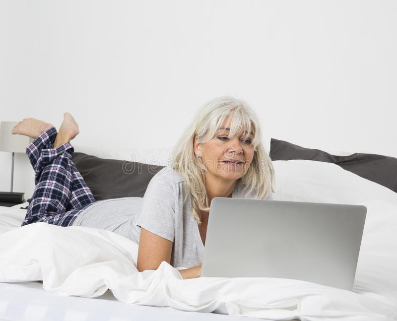 Μέση γυναίκα ηλικίας με ένα lap-top στο κρεβάτι στοκ εικόνες με δικαίωμα ελεύθερης χρήσης