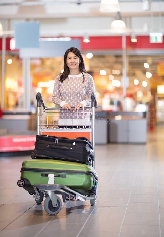 Μέση ενήλικη γυναίκα με τις αποσκευές στο κάρρο στον αερολιμένα στοκ εικόνα με δικαίωμα ελεύθερης χρήσης