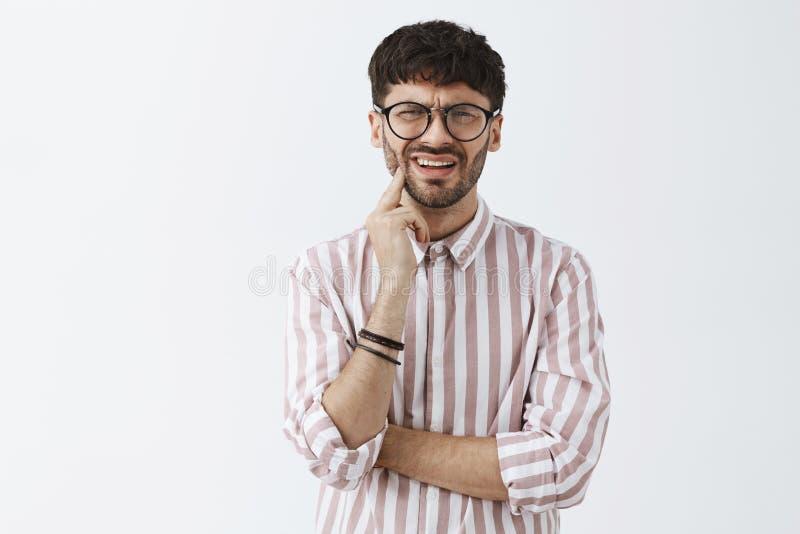 Μέση-επάνω στον πυροβολισμό αβέβαιου το ευρωπαϊκό αρσενικό στο ρόδινο ριγωτό πουκάμισο braceletes και τα γυαλιά που στραβίζουν κα στοκ φωτογραφία με δικαίωμα ελεύθερης χρήσης