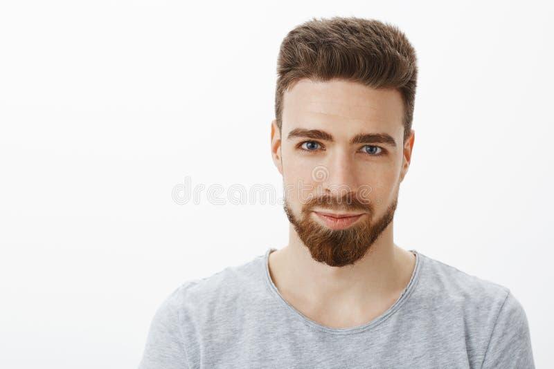 Μέση-επάνω στον πυροβολισμό του όμορφου αισθησιακού και βέβαιου νεαρού άνδρα με τη γενειάδα, moustache και του χαμόγελου μπλε ματ στοκ εικόνες με δικαίωμα ελεύθερης χρήσης