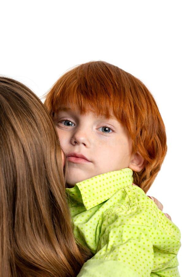 Μέση επάνω στο πορτρέτο του λίγο redhead αγοριού που αγκαλιάζει ήπια το mom του, που απομονώνεται στοκ εικόνες με δικαίωμα ελεύθερης χρήσης