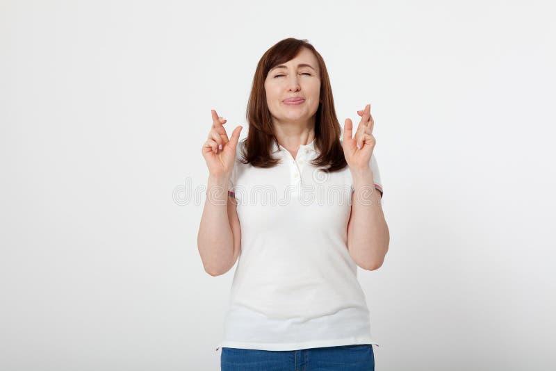 Μέση ηλικίας γυναίκα που διασχίζει τα δάχτυλά της και που επιθυμεί για την καλή τύχη Η κενή άσπρη μπλούζα, χλευάζει επάνω Ημέρα μ στοκ φωτογραφίες με δικαίωμα ελεύθερης χρήσης