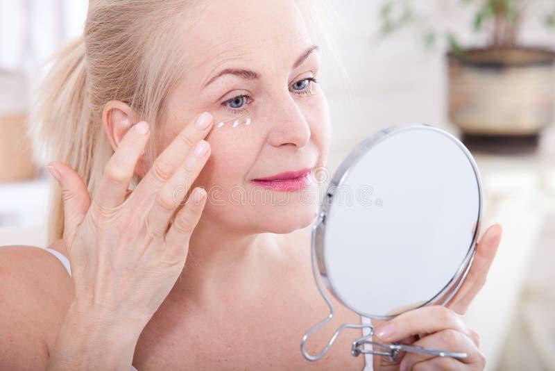 Μέση ηλικίας γυναίκα που εξετάζει τις ρυτίδες στον καθρέφτη Εγχύσεις πλαστικής χειρουργικής και κολλαγόνων makeup Μακρο πρόσωπο ε στοκ φωτογραφία