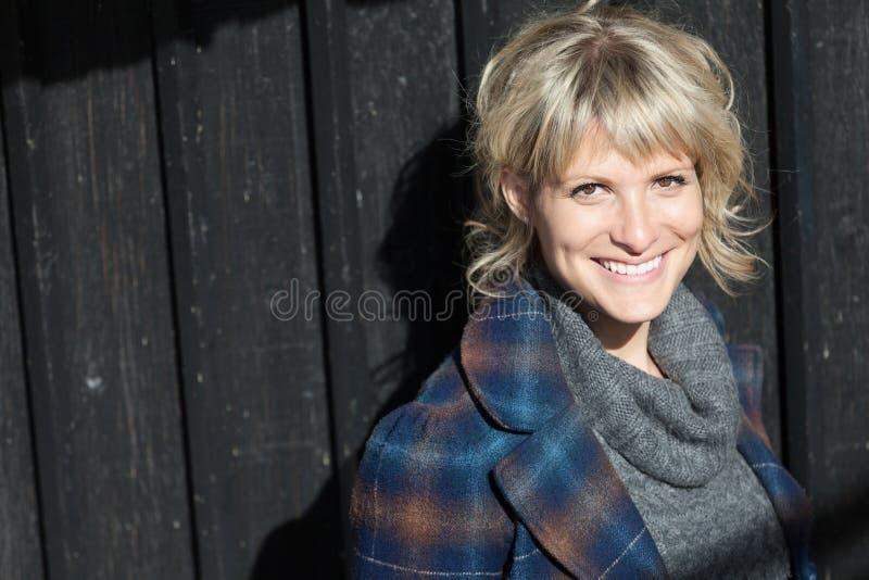 Μέση ηλικίας γυναίκα που χαμογελά στη κάμερα έξω στοκ φωτογραφία