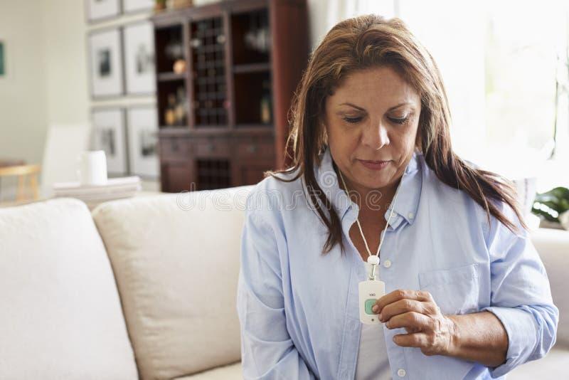 Μέση ηλικίας ισπανική γυναίκα στο σπίτι, που ωθεί έναν συναγερμό βοήθειας που φορά γύρω από το λαιμό της στοκ εικόνες με δικαίωμα ελεύθερης χρήσης