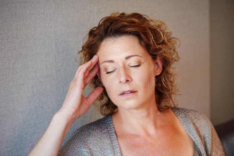 Μέση ηλικίας γυναίκα με το χέρι στο κεφάλι στον πόνο στοκ εικόνα