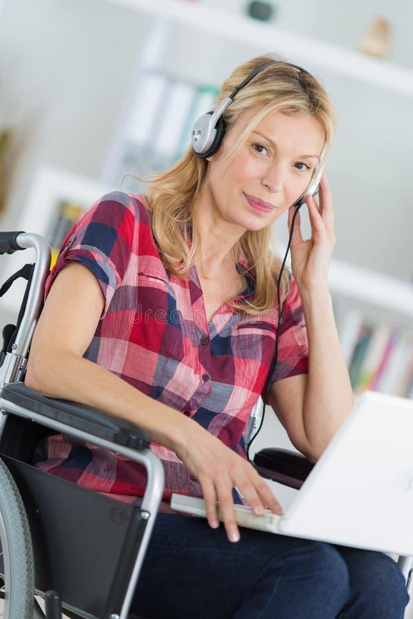 Μέση ηλικίας γυναίκα πορτρέτου στην αναπηρική καρέκλα με το lap-top και τα ακουστικά στοκ εικόνες