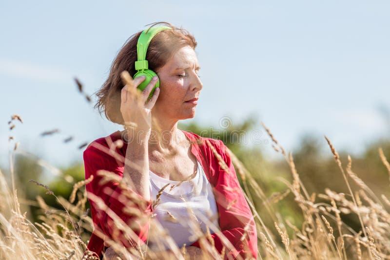 Μέση ηλικίας γυναίκα που απολαμβάνει την ησυχία με τη μουσική υπαίθρια στοκ εικόνα