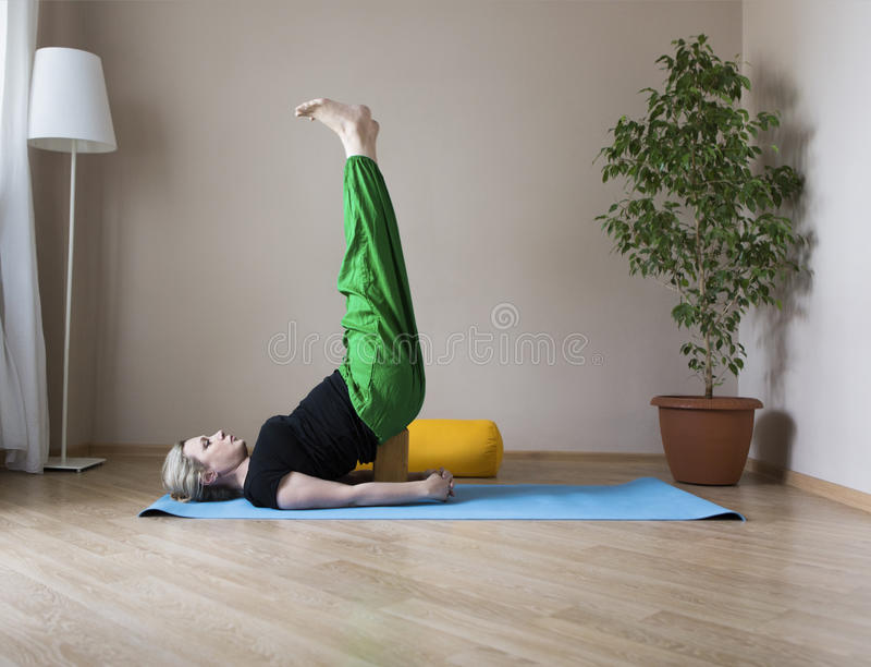 Μέση ηλικίας γυναίκα που κάνει τη γιόγκα στο εσωτερικό στοκ εικόνες
