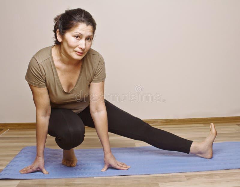 Μέση ηλικίας γυναίκα που κάνει τη γιόγκα στοκ εικόνες