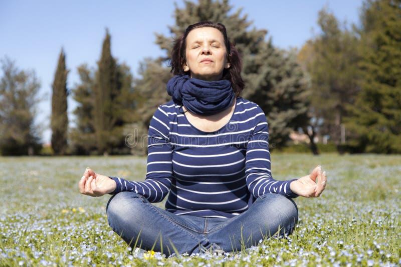 Μέση ηλικίας γυναίκα που κάνει τις ασκήσεις γιόγκας έξω στοκ φωτογραφία
