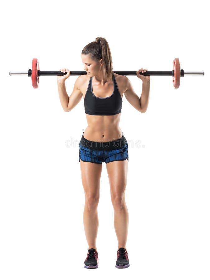 Μέση θέση του αθλητή γυναικών που κάνει την κοντόχοντρη άσκηση Τύπου ώμων με το barbell στοκ φωτογραφία με δικαίωμα ελεύθερης χρήσης