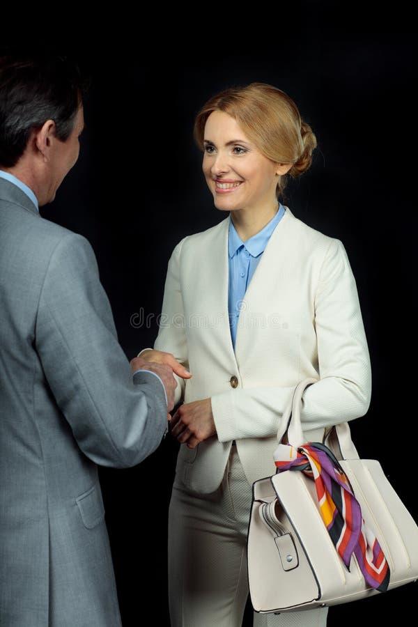 Μέσοι ηλικίας επιχειρηματίας και επιχειρηματίας με τα χέρια τινάγματος τσαντών στοκ εικόνες